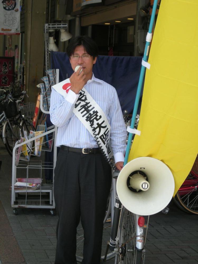 自転車で街宣する熊田氏